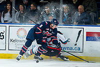 KELOWNA, BC - MARCH 7: Jake Lee #21 of the Kelowna Rockets is checked at the boards by Oliver Okuliar #8 of the Lethbridge Hurricanes during first period at Prospera Place on March 7, 2020 in Kelowna, Canada. (Photo by Marissa Baecker/Shoot the Breeze)