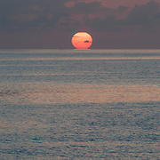 The sun first touches the horizon, with the calm waters of the Coral Sea in the foreground. Taken at Swains Reef on the southern end of the Great Barrier Reef of the coast of Queensland, Australia.