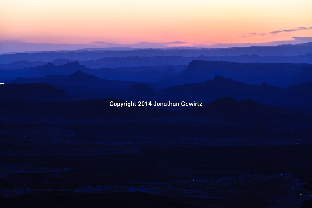 The brightening morning sky silhouettes distant ridges beyond Buck Canyon and the White Rim mesa in Canyonlands National Park, Utah.<br /> <br /> WATERMARKS WILL NOT APPEAR ON PRINTS OR LICENSED IMAGES.<br /> <br /> Licensing: https://tandemstock.com/assets/69607165