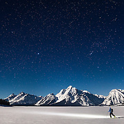 A starlit sky leads to the peaks of the Tetons for a skier on his way to ascent.