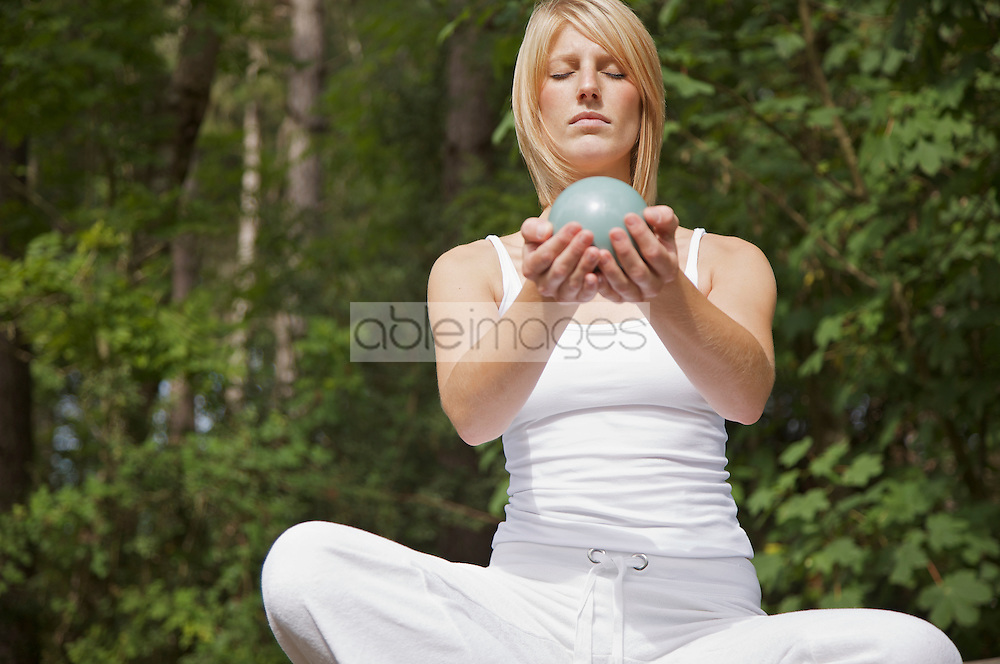 Young woman in meditation sitting cross legged by a forest holding a sphere in her hands