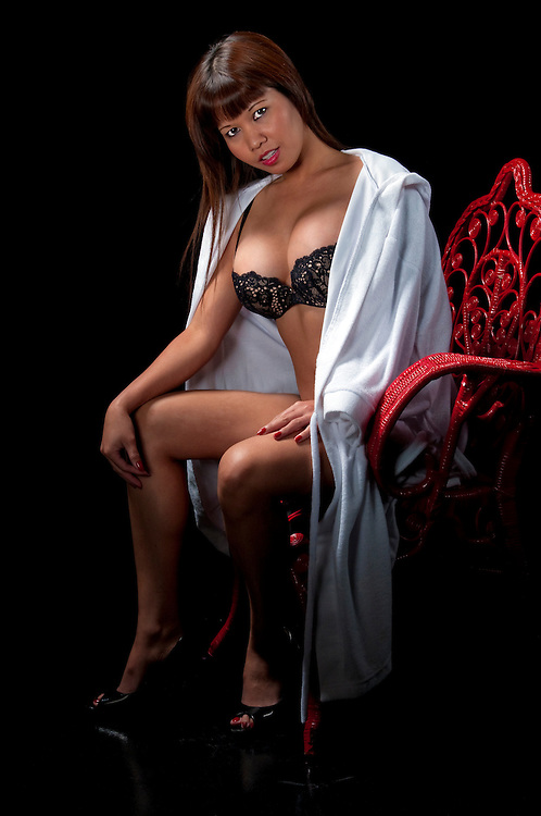 Sensual asian model seated with lingerie and blacl background.