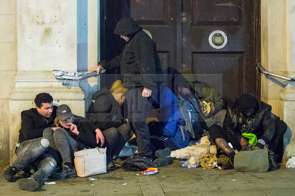 © Licensed to London News Pictures . 07/04/2017 . Manchester , UK . A group of people huddle together in a doorway in Piccadilly . Greater Manchester Police have authorised dispersal powers and say they will ban people from the city centre for 48 hours , this evening (7th April 2017) , in order to tackle alcohol and spice abuse . Photo credit : Joel Goodman/LNP