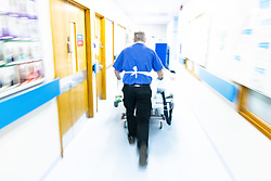 © Licensed to London News Pictures . 18/02/2021. Bury , UK .  A patient is pushing on a trolley along a corridor in the hospital . Inside Fairfield Hospital , where patients are being treated for the effects of Coronavirus . Photo credit : Joel Goodman/LNP
