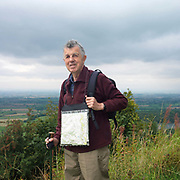 Portrait of a male hiker with a walking pole wears a plastic case with a map inside at Sutton Bank, North York Moors, North Yorkshire, UK