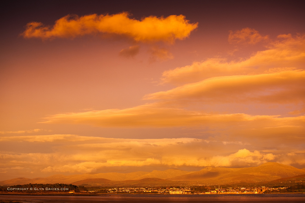 A stunning genuine and unexpected sunset after a stormy afternoon. Different layers of clouds stack high into the sky above the Welsh town of Caernarfon and the mountains of Snowdonia behind. The expansive and dangerously fast Menai Strait lies in the foreground.