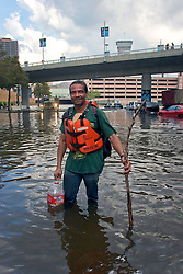 30 August, 2005. New Orleans Louisiana. Hurricane Katrina aftermath. <br /> An evacuee from the storm wades through the flood waters outside the Superdome.<br /> Photo Credit: Charlie Varley/varleypix.com