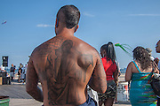 A tattoed man on the boardwalk at Coney Island.