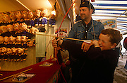 A father helps his young son to fire a bow and arrow at the fairground on Brighton Pier.