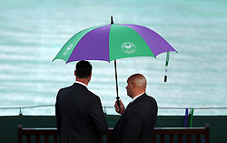 Security shelter under an umbrella during a rain delay on day three of the Wimbledon Championships at the All England Lawn Tennis and Croquet Club, Wimbledon.