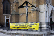 Below an effigy of Christ on the cross is a banner asking passers-by if theyre thinking about joining the Catholic faith in south London, on 21st September 2016, in Waterloo, SE1, London borough of Southwark, England UK.