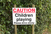 Caution children playing please drive slowly road sign close up, Sutton, Suffolk, England, UK