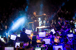 """© Licensed to London News Pictures . 05/02/2016 . Manchester , UK .  """" Hacienda Classical """" debut at the Bridgewater Hall . The 70 piece Manchester Camerata and performers including New Order's Peter Hook , Shaun Ryder , Rowetta Idah , Bez and Hacienda DJs Graeme Park and Mike Pickering mixing live compositions . Photo credit : Joel Goodman/LNP"""