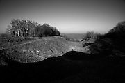 """Argonne Forest WW1, Butte de Vauquois, Meuse-Argonne Battlefield site, France. March 2014<br /> <br /> The mine riven hill, 290 metres high, where German and French forces held trenches either side of the village of Vauquois from October 1914-October 1915. Mines exploded beneth respective positions finally split the hill in two. Nothing of the village remains. The metal frise de cheval barricade still survives.<br /> <br /> The Argonne Forest offensive, part of the final 100 days of WW1 and a major attack on the wetern side of Verdun, was the largest battle in American history up to this point and involved 1.2 million American soldiers.<br /> <br /> Caption information below from Wikipedia:<br /> In the novel """"Birdsong"""", Sebastian Faulks sets his story around the activities of tunnellers on the Western Front, and at Vauquois, we have an area that was riddled with tunnels and saw both French and German engineers and sappers constantly at work.<br /> <br /> The Butte de Vauquois is a small hill, 290 metres high, which dominates the valley between the Argonne massif to the west and the Mort Homme/Hill 304 massif to the east. It allowed good observation in every direction, particularly the Islettes pass leading to Verdun and consequently both German and French Armies were anxious to hold it.<br /> <br /> The Germans first occupied the ridge on 24 September 1914 and subsequently turned it into a fortress supported and flanked by artillery positioned in the woods around Cheppy and Montfaucon.<br /> <br /> Between 28 October 1914, and 28 February 1915, the French made four unsuccessful attacks to remove the Germans from the hill and finally took the German trenches on 1 March 1915 and for the next few days managed to fight off constant German counter-attacks.<br /> <br /> Fighting continued throughout 1915 but neither side made a breakthrough and the front line ran through the village itself. Gradually the two sides decided to abandon hand to hand fighting from the trenche"""