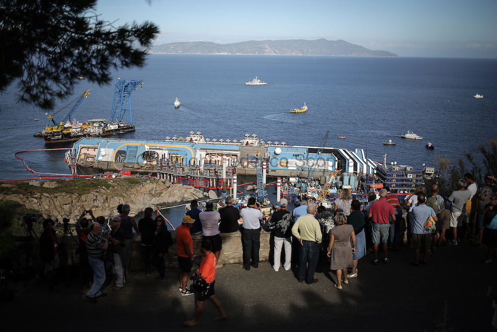 Journalist, turist and local people gather on the hill of Giglio island to assist the Costa Concordia removal operation