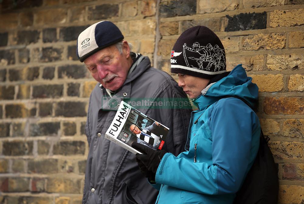 Fulham fans read the match-day programme before the Premier League match at Craven Cottage, London.