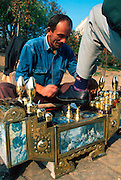 TURKEY, ISTANBUL Man shines shoes near the University; note traditional shoe shine box with photos of popular entertainers and mythology