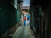 18 FEBRUARY 2015 - BANGKOK, THAILAND: A woman checks her smart phone while she walks down a soi (alley) in the Kudeejeen neighborhood in Bangkok. Santa Cruz church was established in 1770 and is the heart of the community. It is one of the oldest and most historic Catholic churches in Thailand. The church was originally built by Portuguese soldiers allied with King Taksin the Great. Taksin authorized the church as a thanks to the Portuguese who assisted the Siamese during the war with Burma. Most of the Catholics in the neighborhood trace their family roots to the original Portuguese soldiers who married Siamese (Thai) women. There are about 300,000 Catholics in Thailand in about 430 Catholic parishes and about 660 Catholic priests in Thailand. Thais are tolerant of other religions and although Thailand is officially Buddhist, Catholics are allowed to freely practice and people who convert to Catholicism are not discriminated against.          PHOTO BY JACK KURTZ