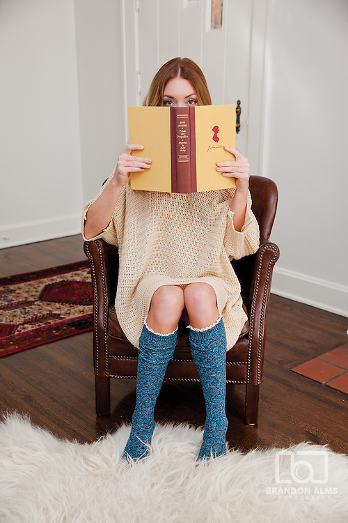 Model posing with a book for an editorial feature.