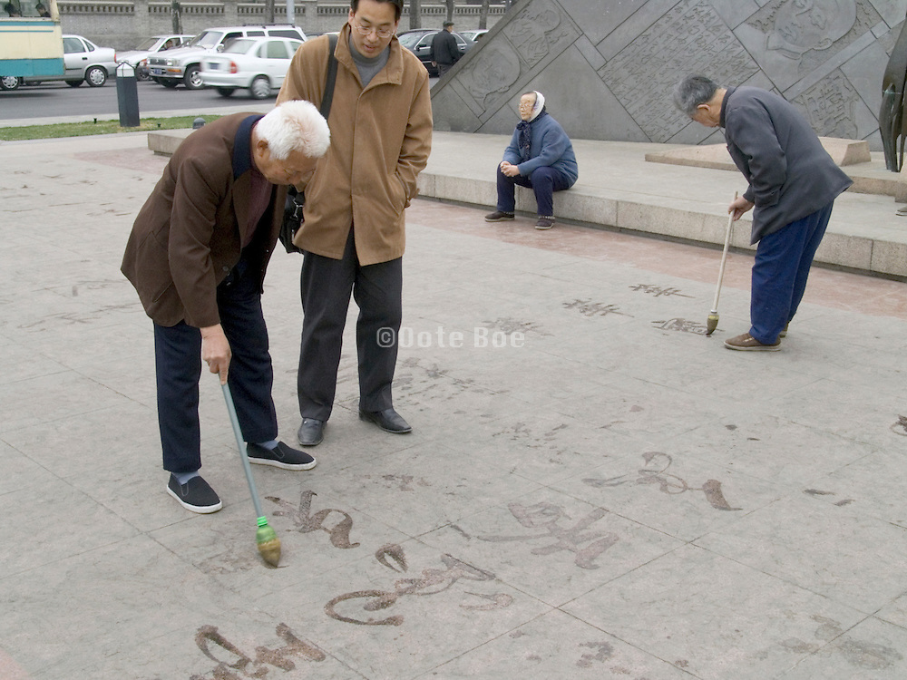 Chinese calligraphy writing with water on pavement Beijing