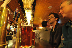 Friends, Brew Beer and Taps at Elephant & Castle, Clay Street, San Francisco, CA. Warm image view of bar surface, taps, hanging glasses and restaurant copper ceiling. With people.
