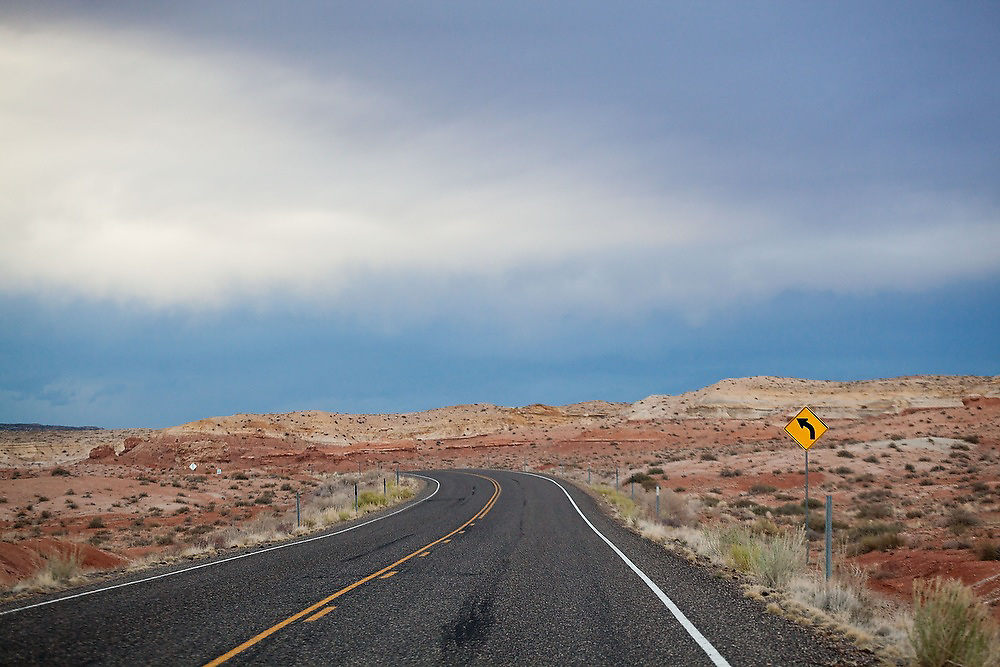 A curved road sign warns of a curving road in the desert near the San Rafael Swell in Utah.