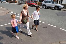 Mother walking children home from school,