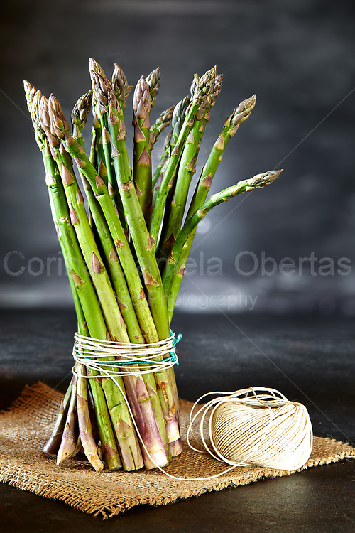 Bunch of asparagus tied with kitchen twine, on a piece of hemp sack. Sold exclusively through Stockfood.com