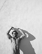 shirtless man against a wall