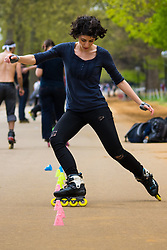 London, April 25th 2015. Despite the threat of forecasted showers, spring sunshine and warmth greets Londoners as they enjoy the Royal Parks in the capital. PICTURED: A woman practices her inline skating skills in Hyde Park.