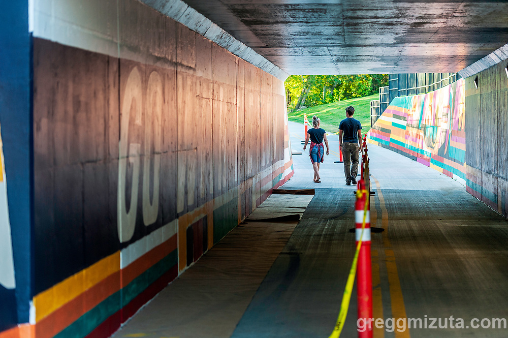 """Kristen Ramirez, Jay Rasgorshek. Go with the Flow, a mural celebrating the 50th Anniversary of the Boise River Greenbelt. Located along the Greenbelt's Fairview Bridge underpass, Boise, Idaho on August 29, 2019.<br /> <br /> The mural is the first of its kind on a section of the pathway managed by the City of Boise.<br /> <br /> Artist Kristen Ramirez landed on the phrase """"go with the flow"""" after meeting with community members and local artists. In addition to having various possible meanings, Ramirez feels it reflects the importance of nature, energy, flow, water, the river, movement, and dynamism in Boise's culture. Of the design, Ramirez says, """"I'm sure you'll see influences from graphic design, modernism, my obsession with all things Mexico (including textiles, color, and architecture), and all the good thinking of the artists of Boise around the type of work they wish to see.""""<br /> <br /> The mural is a collaboration with local artists Ellen Wilson, Eva Streicher, Jay Rasgorshek, Julia Green, Justin W. John and Nicolet Laursen."""