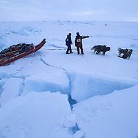INTERNATIONAL ARCTIC PROJECT.  Julie Hansen & Takako Takano wait for Victor Boyarsky to scout route thru pressure ice on frozen Arctic Ocean.