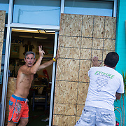 WRIGHTSVILLE BEACH, NC - SEPETEMBER 11,  2018:  Jazz Undy, owner of Wrightsville Beach Art Co, waves to a friend as he helps board up his shop in anticipation of Hurricane Florence. Logan Cyrus for AFP
