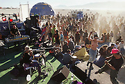 At dawn after the night of the burn, dancers still move to techno music in the Black Rock Desert at Burning Man. Burning Man is a performance art festival known for art, drugs and sex. It takes place annually in the Black Rock Desert near Gerlach, Nevada, USA. Dawn after the burning of the giant man, dancing to Techno music.