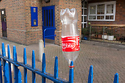 Coca Cola bottle disgarded on a metal fence on a council block in East London, UK.