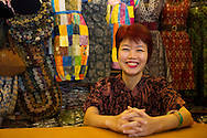 Smiling female proprietor of a small textiles shop in Surakarta, Central Java, Indonesia.