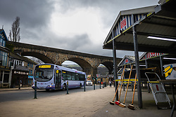 """© Licensed to London News Pictures . 19/03/2021. Todmorden , UK . A 589 bus with signage reading """" This bus is full due to social distancing """" passes under a railway viaduct running through Todmorden Town Centre adjacent to the town's covered outdoor market , alongside signage urging pedestrians to """" Stay 2m apart """". Exploring a year of experiences , lessons and consequences of Coronavirus in the NW of England . Photo credit : Joel Goodman/LNP"""