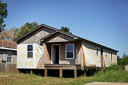 26 August 2015. New Orleans, Louisiana. <br /> Hurricane Katrina revisited. <br /> A partially finished and then abandoned home in the Lower 9th Ward. Many people tried and failed in their bids to return after falling victim to unscrupulous contractors, insurance companies paying cents on the dollar and a number of other factors that drained their finances and prevented them form finishing their dream homes in their old neighborhoods. <br /> Photo credit©; Charlie Varley/varleypix.com.