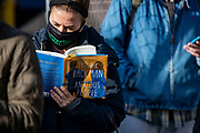 Kaitlin Straits reads an aptly-named book while waiting on line to vote Monday, Nov. 2, 2020 at Pulaski Elementary School in Bucktown on the last day of early voting in Chicago. (Brian Cassella/Chicago Tribune)