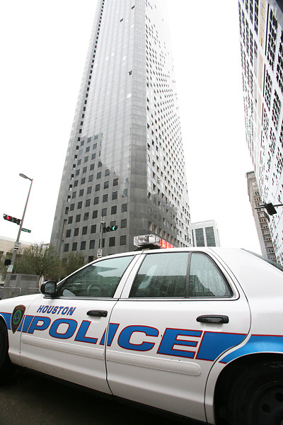 Stock photo of a Houston police cruiser parked in downtown Houston in front of buildings who's windows have been damaged by Hurricane Ike's winds