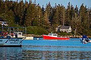 A red lobster boat moored in the quaint fishing harbor of Port Clyde, Maine.
