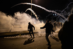 "© Licensed to London News Pictures. 22/01/2020. Beirut, Lebanon. Demonstrators throw tear gas canisters back to police on Martyrs' Square, Beirut, during a riot following the announcement late last night that a government has been formed. Police respond with tear gas and water cannon against the anti-government demonstrators. Violence has been escalating in the capital following a ""week of wrath"", where demonstrators were campaigning against government corruption and economic crisis. Photo credit : Tom Nicholson/LNP"
