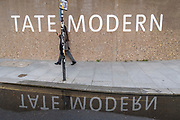A woman who is using her phone, a woman walks past Brutalist concrete architecture Tate Modern art gallery on the Southbank, on 26th October 2020, in London, England.