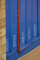 Blue hall locker in a school hallway has a sprung door.