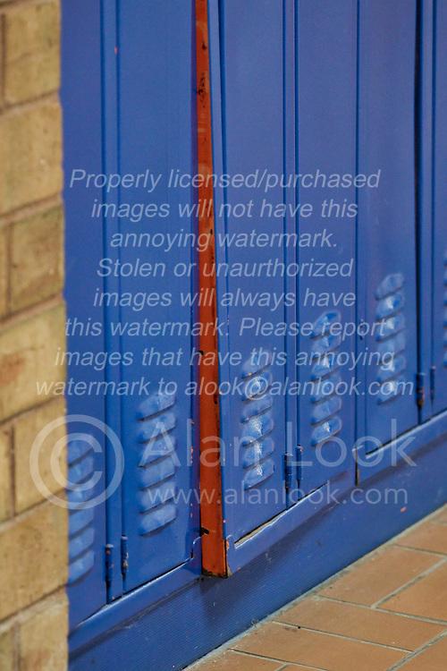 Blue hall locker in a school hallway has a sprung door.