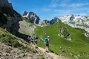 Hikers at Bötzel pass contemplate the distant peak of Santis, in Switzerland, Europe. Shared by three cantons, Säntis (2502 m) is the highest mountain in the Alpstein massif of northeastern Switzerland, and highest of the Appenzell Alps, which rise between Lake Walen and Lake Constance. Accessible via cable car or spectacular trails, Säntis provides a spectacular view across six countries: Switzerland, Germany, Austria, Liechtenstein, France and Italy.