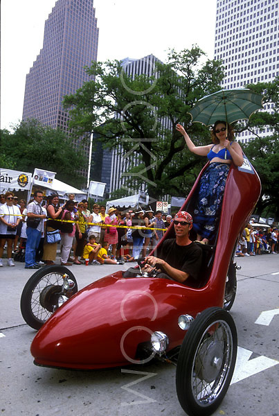 Stock photo of a man and woman riding in a red stiletto car