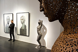 © Licensed to London News Pictures. 13/09/2018. London, UK. Artist NICK GENTRY poses with his work titled Human Connection (L) and Being 2 (R), 2018. The bicycle chain sculpture is titled Iron chain (Rust) 2013 by artist SEO Young-Deok. Nick paints portraits on top of obsolete technological materials such as VHS cassettes and floppy disks that contain people's memories. His work is part of a joint exhibiton with South Korea artist SEO YOUNG-DEOK at the Opera Gallery. Photo credit: Ray Tang/LNP
