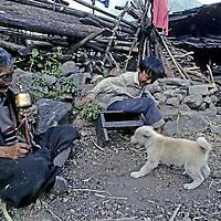 CHINA, TIBET.  Menba Grandmother & grandson play with puppy in Payi village near mouth of Tsangpo River Gorge (eastern Himalaya). Note Buddhist prayer wheel.