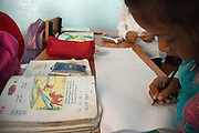A girl draws a yurt at School 110 Boston, in Osh (Kyrgyzstan), where Save the Children supports a child-friendly space.
